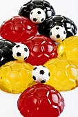 Black, red and yellow jellies in shape of footballs
