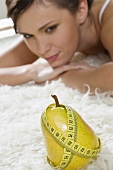 Young woman looking at pear with tape measure