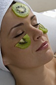 Young woman with slices of kiwi fruit on her face