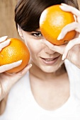 Young woman holding two oranges in front of her face