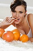 Young woman on a bed with oranges and grapefruits
