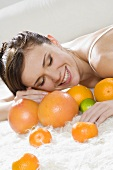 Young woman on a bed with citrus fruit