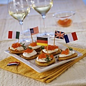 Blinis with fresh cheese, trout caviare and flags