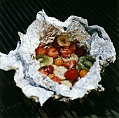 Fruit in aluminium foil on grill rack