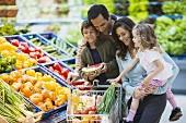 Familie mit vollem Einkaufswagen am Gemüsestand im Supermarkt