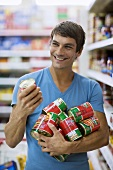 Young man buying tinned tomatoes in a supermarket