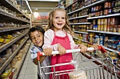 Two children with a shopping trolley in a supermarket