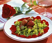 Plate of fresh strawberries, rose petals and lady's mantle