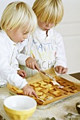 Two children brushing biscuits with glacé icing