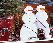 Wooden snowmen on a garden bench