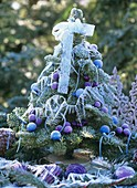 Small decorated Christmas tree with hoar frost