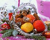 Äpfel, Tannen- und Kiefernzapfen in einem Weidenkorb