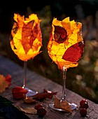 Wine glasses with tea lights, with colourful autumn leaves