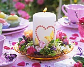 Flower wreath around candle with heart motif on plate