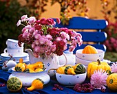 Autumn flowers in teapot and ornamental gourds
