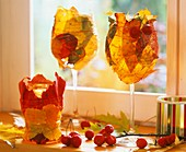 Wine glasses wrapped with autumn leaves and wire