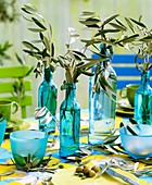 Olive branches in bottles as table decoration