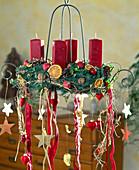 Hängender Adventskranz mit roten Kerzen und Bändern