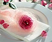 Serviettendeko mit Rosenblüte und weißem Engelshaar