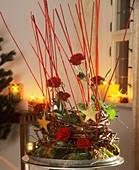 Gesteck aus Rosenzweigen und Rosenblüten