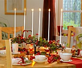 Festive table decoration with rose hips & nuts for Advent tea