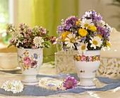 Sträusse aus Margeriten, Trollblumen, Schleifenblume, Storchschnabel, Zierlauch, Flockenblumen und Vergißmeinnicht