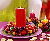 Rote Kerze im Tellerkranz aus Scheinzypresse und bunte Kugeln