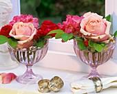 Rosen und Rhododendron in Glasbechern
