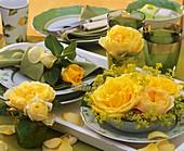 Gelbe Rosen und Frauenmantel auf gemustertem Geschirr