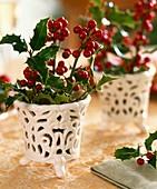 Stechpalmenzweig in kleinen Vasen
