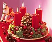 Adventskranz aus Zapfen und Moos mit roten Kerzen