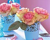 Rosen in blauen Blechtöpfen als Tischdeko