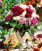 Autumn arrangement of chrysanthemums, asters, roses and ivy