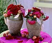 Roses & ornamental apples in two nostalgic vases on garden table