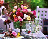 Luxuriant bouquet in garden with roses, rose hips & Clematis