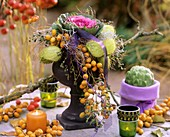 Arrangement of ornamental cabbage, silkweed fruits & dates