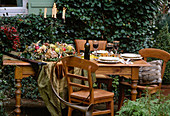 Table with autumn wreath of fruit and nuts