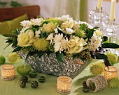 Gesteck von Zierkohl, Chrysanthemen und tropischen Früchten