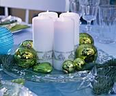 Glasteller mit weissen Kerzen und Christbaumkugeln