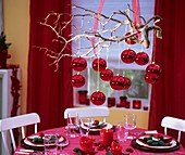 Red baubles on branch hanging over table