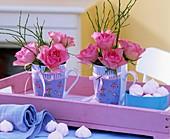 Kleine Rosensträusse in Tassen auf einem Tablett