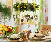Table laid for Easter with soup bowls; hanging wreath