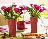 Flockenblumen mit Rosmarin in Vasen, Waffeln und Tassen