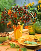 Vase of hawkweed; bowl with floating candles; biscotti