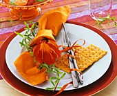 Place-setting with orange napkin, fire lily & crispbread
