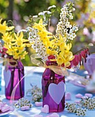 Narcissi, Spiraea and bleeding heart in glass bottle