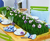 Table runner of wheat grass & pansies on table laid for coffee