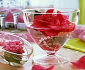 Glasschale mit Kamelienblüten und Perlenkette