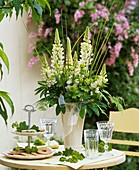 Vase of white lupins, tiered stand with biscuits