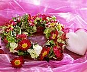 Kranz aus Primel- und Hortensienblüten, daneben Herz